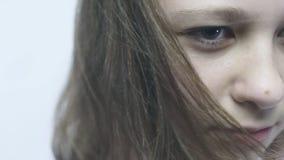 Retrato do close-up de uma menina restrita nova Uma menina bonita com olhos grandes está estando no vento no slowmo vídeos de arquivo