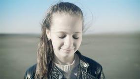 Retrato do close-up de uma menina de sorriso nova Uma menina doce olha a câmera e ri filme