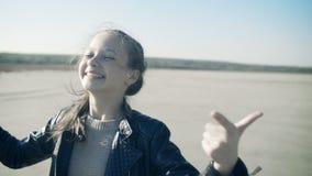 Retrato do close-up de uma menina de sorriso nova Uma menina doce olha a câmera e ri video estoque