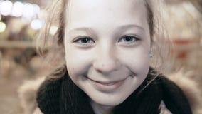 Retrato do close-up de uma menina de sorriso nova feliz que olha a câmera Menina bonita na rua, a luz nela video estoque