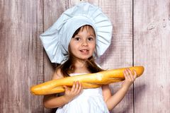 Retrato do close-up de uma menina de sorriso pequena em um tampão de cozimento com um baguette fresco em suas mãos fotografia de stock