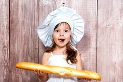 Retrato do close-up de uma menina de sorriso pequena em um tampão de cozimento com um baguette fresco em suas mãos imagem de stock royalty free