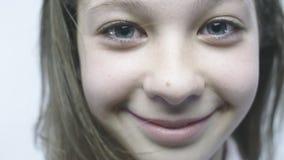 Retrato do close-up de uma moça alegre Uma menina bonita com olhos grandes está estando no vento no slowmo video estoque