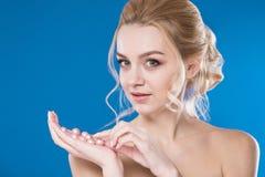 Retrato do close-up de uma moça em um fundo azul Imagens de Stock