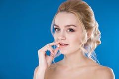 Retrato do close-up de uma moça em um fundo azul Foto de Stock