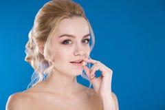 Retrato do close-up de uma moça em um fundo azul Fotos de Stock