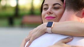 Retrato do close-up de uma moça que abrace seu indivíduo amado em um parque do verão filme