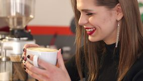 Retrato do close-up de uma moça de riso em uma cafetaria com uma xícara de café video estoque