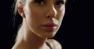 Retrato do close-up de uma mulher loura bonita no equipamento do exercício filme