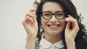 Retrato do close-up de uma mulher de negócio moreno bonita nova surpreendida A boca e os olhos são abertos nos vidros, isolados vídeos de arquivo