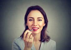 Retrato do close up de uma mulher que aplica o batom da composição fotos de stock