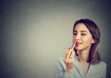 Retrato do close up de uma mulher que aplica o batom da composição imagem de stock royalty free