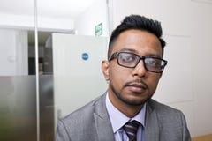 Retrato do close-up de vidros vestindo do homem de negócios indiano com barba Foto de Stock Royalty Free