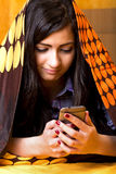 Retrato do close up do adolescente bonito que usa o telefone de mobil escondido fotografia de stock royalty free