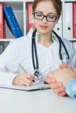 Retrato do close up do doutor fêmea que toma notas na história médica Fotografia de Stock Royalty Free