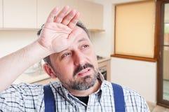 Retrato do close up do encanador masculino com dor de cabeça imagem de stock