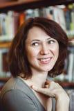 Retrato do close up do estudante de mulher maduro de sorriso da Idade Média na biblioteca que olha afastado, profissão do bibliot fotos de stock