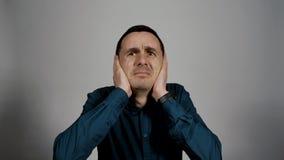 Retrato do close up dos gestos novos do homem de negócio que cobrem as orelhas do ruído alto vídeos de arquivo
