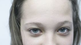 Retrato do close-up dos olhos azuis de uma moça Uma menina bonita com olhos grandes está estando no vento no slowmo vídeos de arquivo