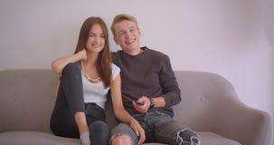 Retrato do close up dos pares caucasianos bonitos novos que olham a tevê rir felizmente o assento no sofá dentro no vídeos de arquivo