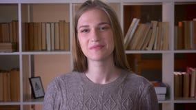 Retrato do close up do estudante fêmea atrativo novo que olha a câmera e que sorri felizmente com excitamento na faculdade filme