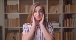 Retrato do close up do estudante fêmea caucasiano bonito novo que sorri com o excitamento que olha a câmera na faculdade filme