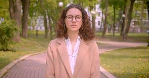 Retrato do close up do estudante fêmea caucasiano encaracolado de cabelos compridos novo nos vidros que olham a câmera que está f filme