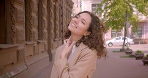 Retrato do close up do estudante fêmea caucasiano encaracolado de cabelos compridos novo que sorri felizmente levantando na frent video estoque