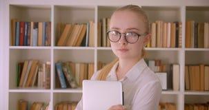 Retrato do close up do estudante fêmea louro caucasiano bonito novo nos vidros que guardam um portátil que olha o sorriso da câme vídeos de arquivo