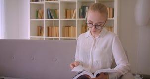 Retrato do close up do estudante fêmea louro caucasiano bonito novo nos vidros que lê um livro e que olha o assento da câmera video estoque