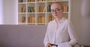 Retrato do close up do estudante fêmea louro caucasiano bonito novo nos vidros que lê um livro e que olha o sorriso da câmera vídeos de arquivo