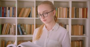 Retrato do close up do estudante fêmea louro caucasiano bonito novo nos vidros que lê um livro que está dentro no vídeos de arquivo