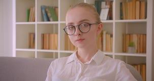 Retrato do close up do estudante fêmea louro caucasiano bonito novo nos vidros que olham a câmera que senta-se no sofá vídeos de arquivo