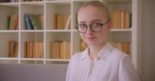 Retrato do close up do estudante fêmea louro caucasiano bonito novo nos vidros que olham a câmera que sorri alegremente sentando- filme