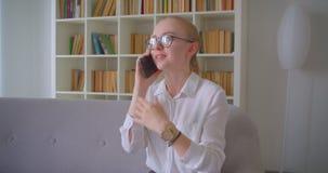 Retrato do close up do estudante fêmea louro caucasiano bonito novo nos vidros que têm um telefonema que senta-se no sofá filme