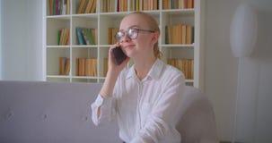 Retrato do close up do estudante fêmea louro caucasiano bonito novo nos vidros que têm um telefonema que sorri alegremente video estoque