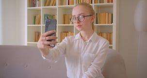 Retrato do close up do estudante fêmea louro caucasiano bonito novo nos vidros que tomam selfies no telefone que senta-se no vídeos de arquivo