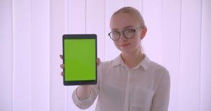 Retrato do close up do estudante fêmea louro caucasiano bonito novo nos vidros usando a tabuleta e mostrando o croma verde video estoque