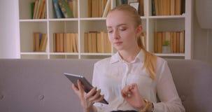 Retrato do close up do estudante fêmea louro caucasiano bonito novo que usa a tabuleta e mostrando a tela verde à câmera video estoque