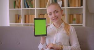 Retrato do close up do estudante fêmea louro caucasiano bonito novo que usa a tabuleta e mostrando a tela verde do croma a filme