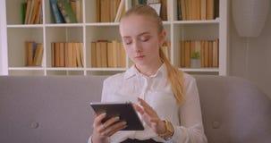 Retrato do close up do estudante fêmea louro caucasiano bonito novo que usa a tabuleta que olha a câmera que sorri alegremente video estoque