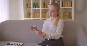 Retrato do close up do estudante fêmea louro caucasiano bonito novo que usa a tabuleta que senta-se no sofá dentro no vídeos de arquivo