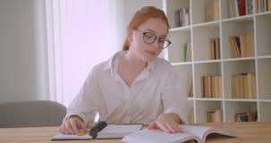 Retrato do close up do estudante fêmea do ruivo bonito novo nos vidros com rabo de cavalo usando a tabuleta e escrevendo na vídeos de arquivo