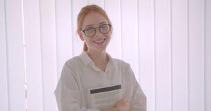 Retrato do close up do estudante fêmea do ruivo bonito novo nos vidros que guardam um livro que olha a posição da câmera no video estoque