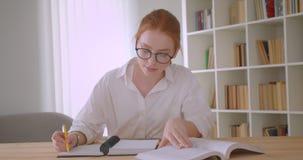 Retrato do close up do estudante fêmea do ruivo bonito novo nos vidros usando a tabuleta e escrevendo em um caderno que senta-se  vídeos de arquivo