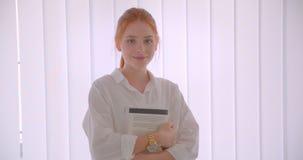 Retrato do close up do estudante fêmea do ruivo bonito novo que guarda um livro que olha a posição da câmera na sala branca filme