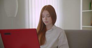 Retrato do close up do estudante fêmea do ruivo bonito novo que usa o portátil e estudando em linha a vista do assento da câmera vídeos de arquivo