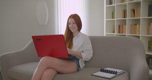 Retrato do close up do estudante fêmea do ruivo bonito novo que usa o portátil e estudando o sorriso em linha felizmente sentando filme