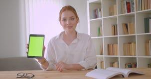 Retrato do close up do estudante fêmea do ruivo bonito novo que usa a tabuleta e mostrando a tela verde à câmera que senta-se em video estoque