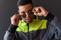 Retrato do close up do homem afro-americano à moda que olha com do levantamento para óculos de sol do espelho, levantando na pare foto de stock royalty free